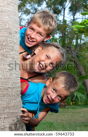 Three children look out from behind a palm, summer. - stock photo