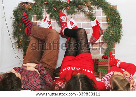 Three children lying on the backs with their legs lifted up near Christmas decorated fireplace, winter holiday family concept, focus on the socks - stock photo