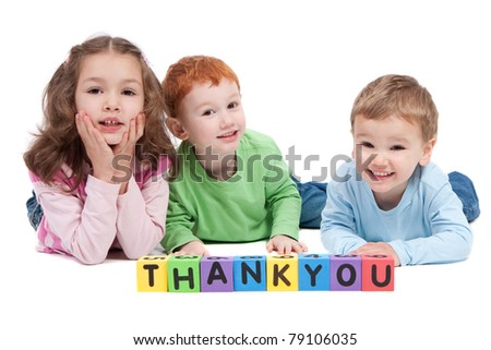 Three children lying saying thankyou with kids letter blocks. Isolated on white. - stock photo