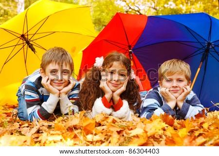 Three children lying under three colorful umbrellas - stock photo