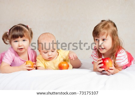 Three children of different age with apples - stock photo