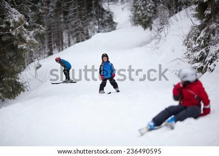 Three children on the ski slope - stock photo