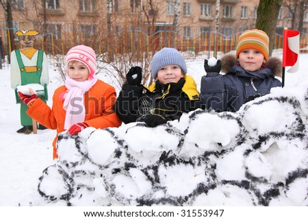Three children on wall of  snow fortress in  court yard throw snowballs - stock photo