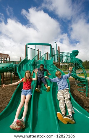 Three children playing on a green slide under a beautiful sky. A wide angle lens creates comic distortion of the foreground. - stock photo