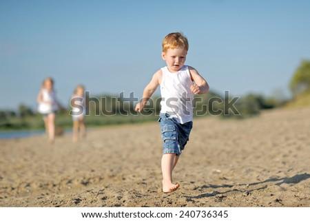 three children playing on beach in summer - stock photo