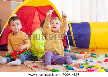 three children playing on  floor with colored toys.  - stock photo
