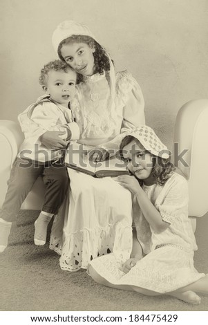 Three children posing in victorian clothes in vintage style - stock photo