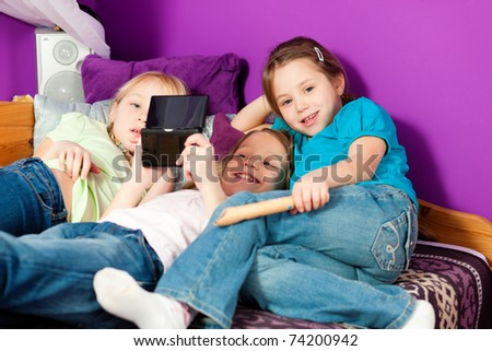 Three children � sisters - playing video games in their room - stock photo