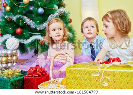 Three children sit in room under christmas tree with gift boxes, focus on left girl