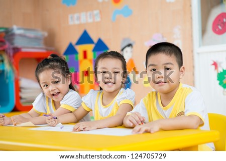 Three children sitting behind the desk and smiling - stock photo