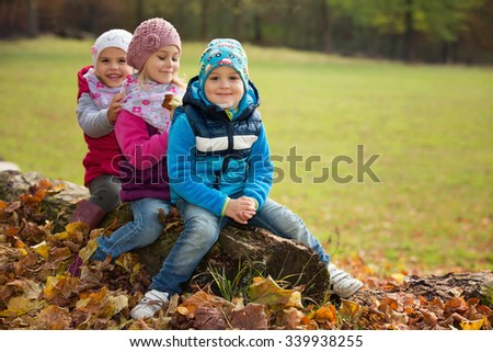 Three children sitting in a park on a tree trunk - stock photo