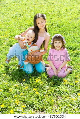 Three children sitting on the grass in the sun