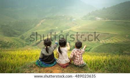Three children sitting side by side, back view to point to Rice fields on terraced of Mu Cang Chai, YenBai, Vietnam. Rice fields prepare the harvest at Northwest Vietnam.Vietnam landscapes.