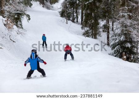 Three children skiing down the ski slope. Back view - stock photo