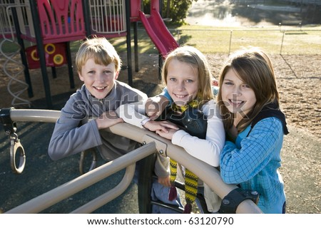 Three children (10 to 11 years) standing together on playground equipment