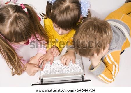 Three children typing on laptop keyboard - stock photo
