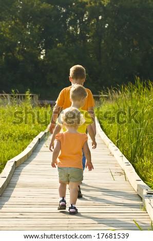 Three Children walk the Dock in the Morning - stock photo