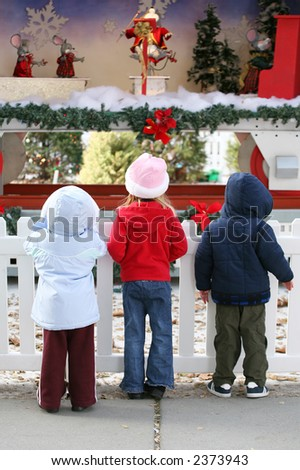 Three children watching the Christmas display in the park