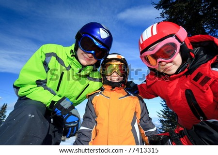 Three children wearing colorful ski goggles and winter jackets outdoors.