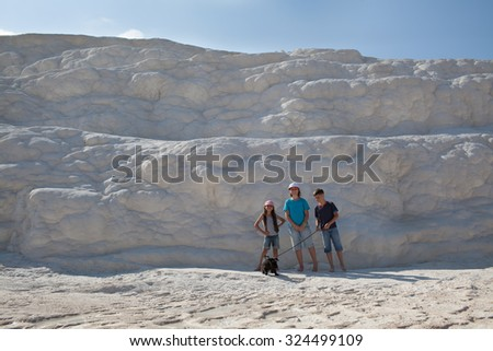 Three children with dog standing on limestone wall in Pamukkale, Turkey