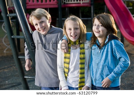 Three children (10-11 years) standing together on playground on chilly day