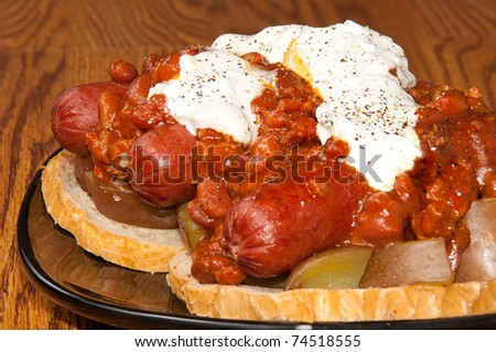 Three Chili dogs on top of potatoes and bread, covered in Sour Cream, Hot Sauce and Pepper - stock photo