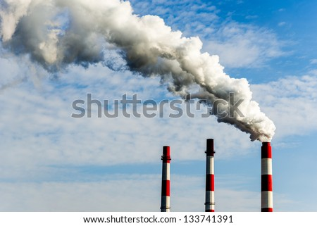 three chimneys of a power plant, one with heavy smoke - stock photo