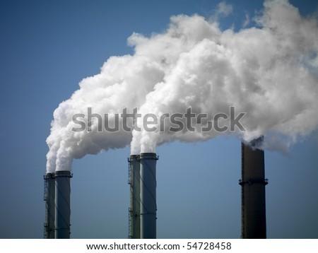 Three chimneys with smoke - stock photo
