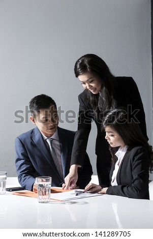 Three Chinese Business people meeting in office to discuss a project - stock photo