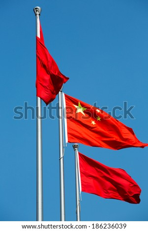 Three Chinese national flag within a blue sky, low angle photographs taken in Shanghai. - stock photo