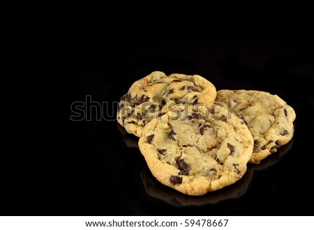 Three Chocolate Chip cookies on black background with copy space - stock photo