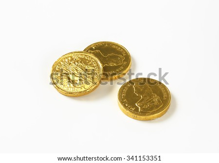 three chocolate coins on white background - stock photo