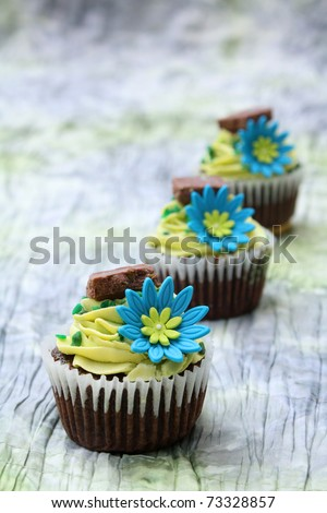 Three chocolate cupcakes decorated with icing and flowers - stock photo
