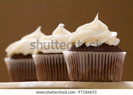 Three chocolate cupcakes with a brown background - stock photo