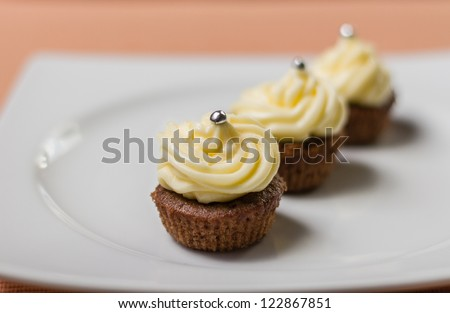 Three chocolate cupcakes with silver sprinkles on top, on white plate and fabric tablecloth - stock photo