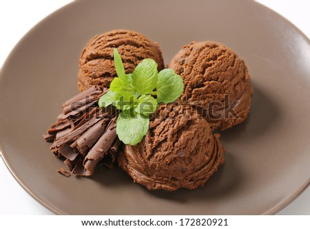 three chocolate ice cream scoops with chocolate flakes and herbs, served on a plate