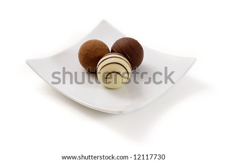 Three chocolate truffle in a white plate isolated over a white background - stock photo