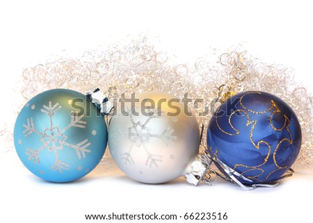 Three Christmas balls and golden tinsel. Isolated on white