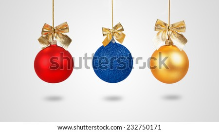 Three Christmas balls with golden bows isolated on white background - stock photo