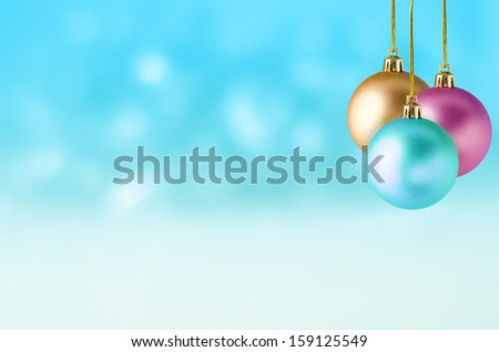 Three Christmas baubles in turquoise, pink and gold, hanging at different lengths in a group against a soft bokeh background of turquoise and white, with the appearance of falling snow. - stock photo