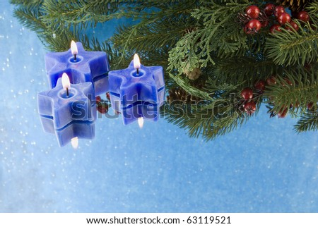 three Christmas blue star shaped candles with fir branch, reflections, and copyspace