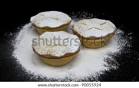 Three Christmas Mince Pies with stars sprinkled with icing sugar - stock photo