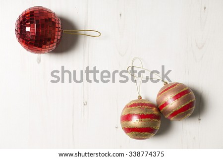 Three Christmas mirrored baubles on a light wooden surface - stock photo