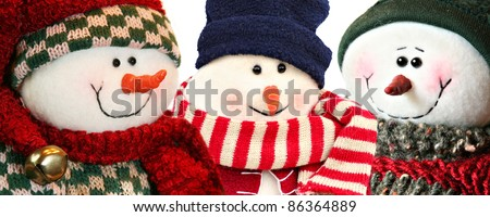 Three Christmas snowman wearing knitted hats and scarves. - stock photo