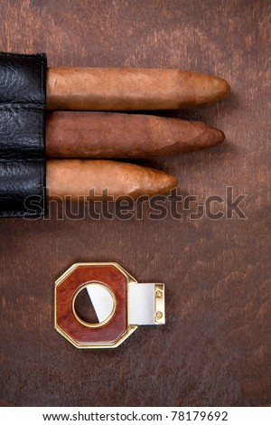 three cigars and cutter on a dark background - stock photo