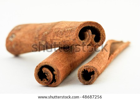 Three cinnamon sticks isolated on white background. Close up. - stock photo