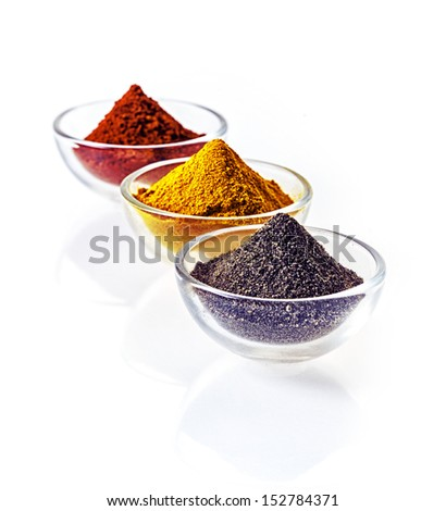 Three clear glass bowls of colourful of ground spice and black lava salt in conical heaps arranged in a receding row on a white background - stock photo