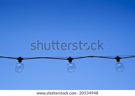 Three clear round light bulbs hanging against a blue summer sky