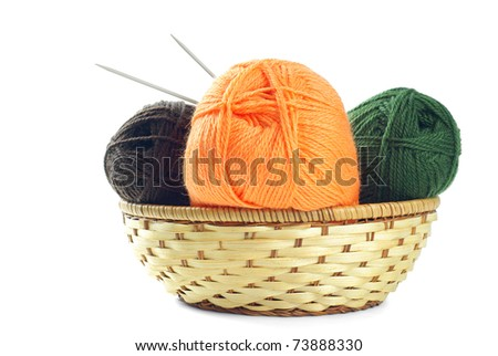 Three clews of woolen yarn in wicker basket over pure white background - stock photo