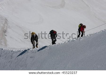 Three climbers ascent over a ridge - stock photo
